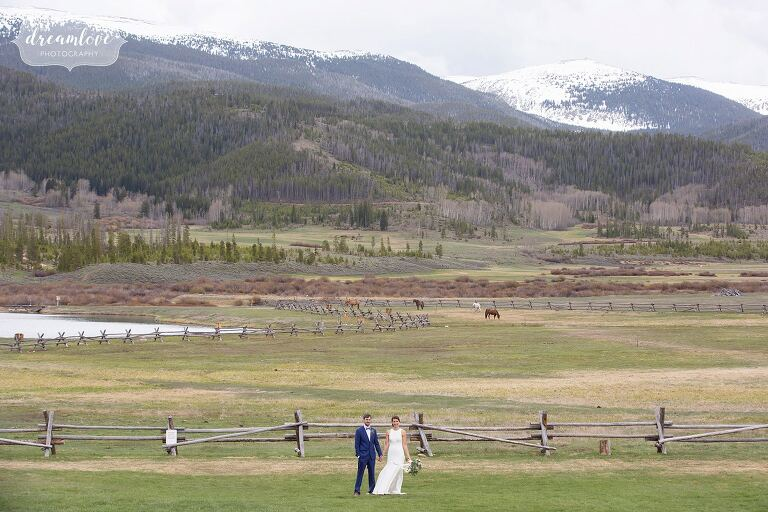 Bride and groom stand in field at Devil's Thumb Ranch surrounded by mountains and horses.