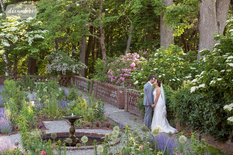 Bride and groom kiss in historic garden of Bradley Estate in Canton, MA.