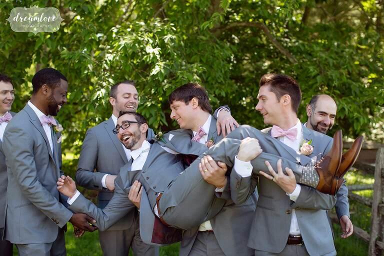 Funny groomsmen carrying groom at estate wedding venue in Boston.