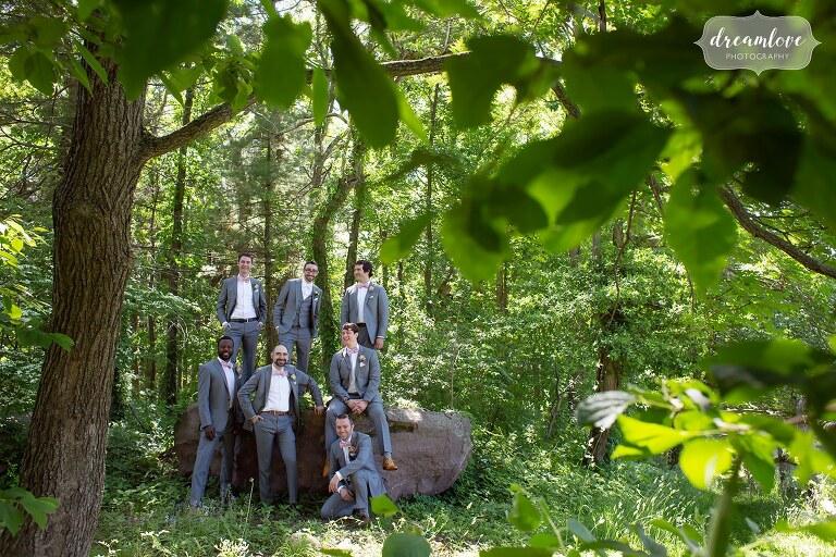 Fashion wedding photo of groomsmen in the woods on rock.