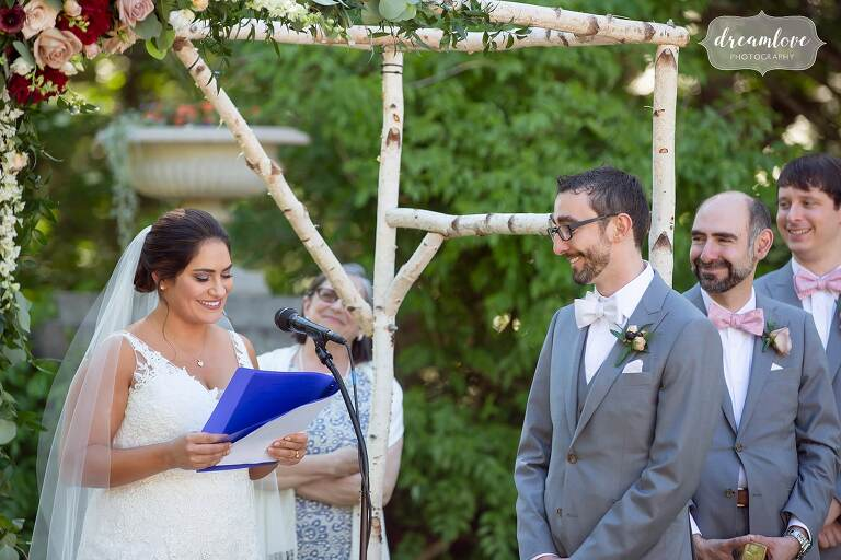 Bride reads her vows to smiling groom.
