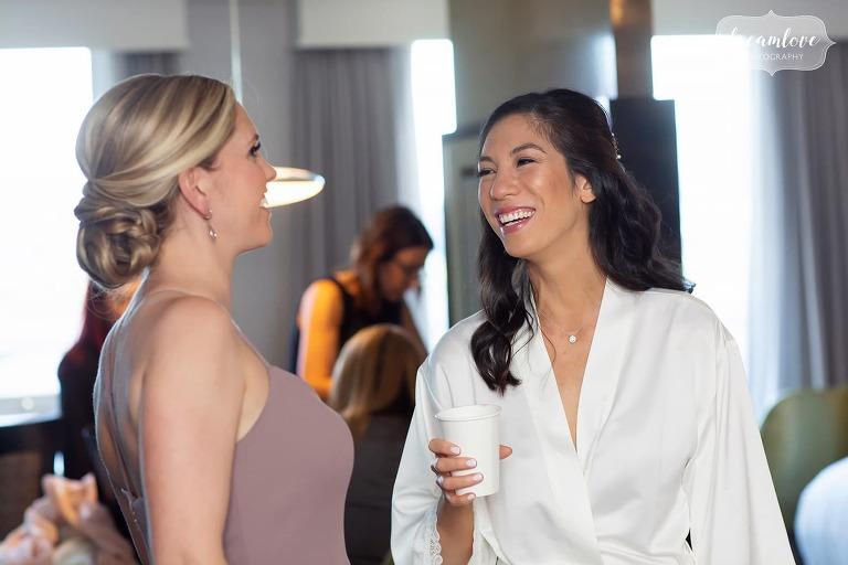 Bride laughing with bridesmaid at Hotel Sonesta in Cambridge, MA.