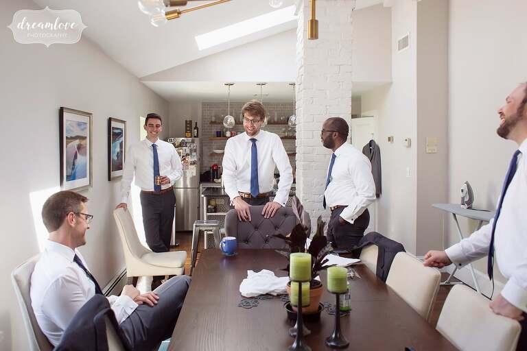 Groomsmen relax and drink coffee before Boston estate wedding.