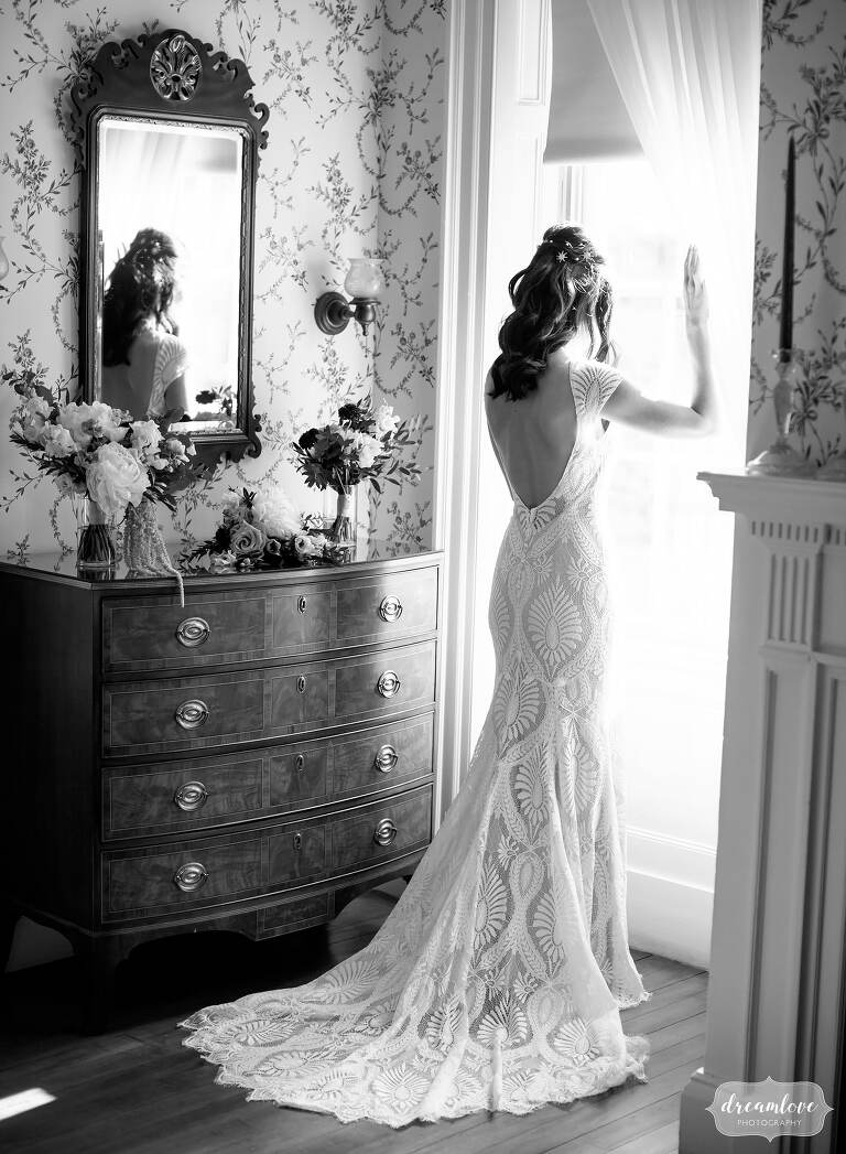 Bride looking out window of Lyman Estate in modern BHLDN Ludlow dress with pattern.