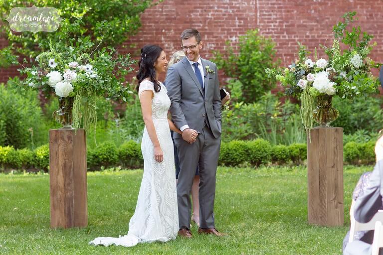 Groom smiles at bride during outdoor summer wedding ceremony at Lyman Estate.