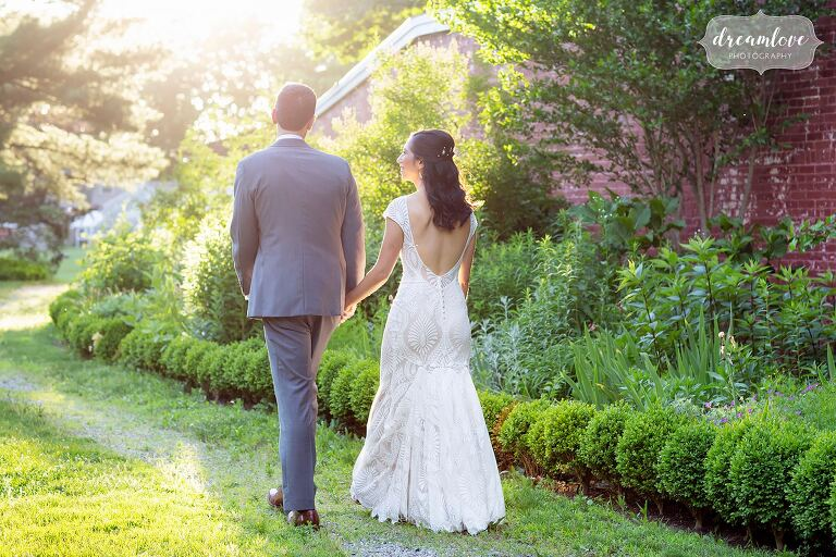 Bride and groom walk into the sunset at Lyman Estate gardens.