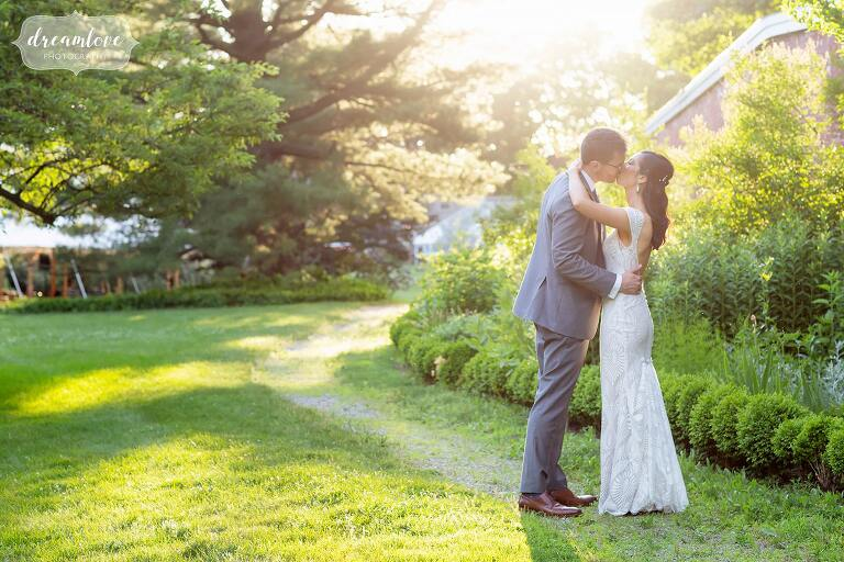 Bride and groom kiss on a winding path at Lyman Estate.