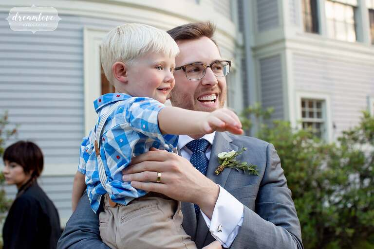 Groom holds up little boy at Lyman Estate.