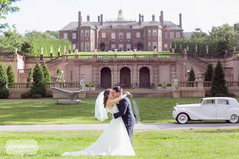 Bride and groom kiss in front of grand estate, captured by north shore wedding photographers.