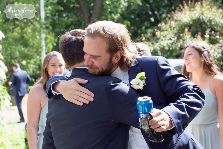 Groomsman hugs groom after ceremony in Danvers, MA.