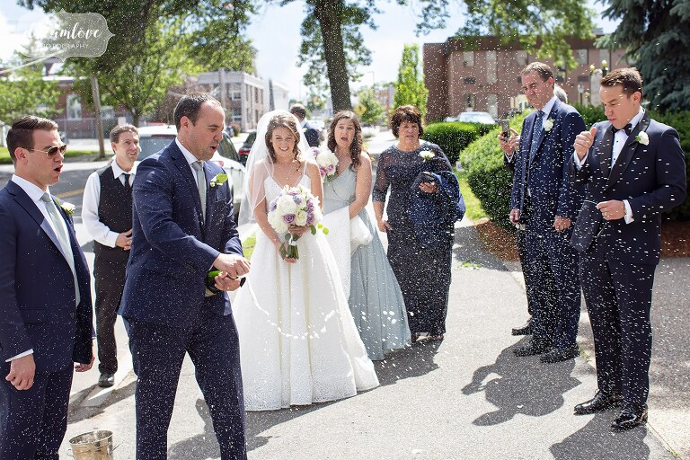 Funny photo of the bride and groom sprayed in champagne after wedding ceremony in Danvers, MA.