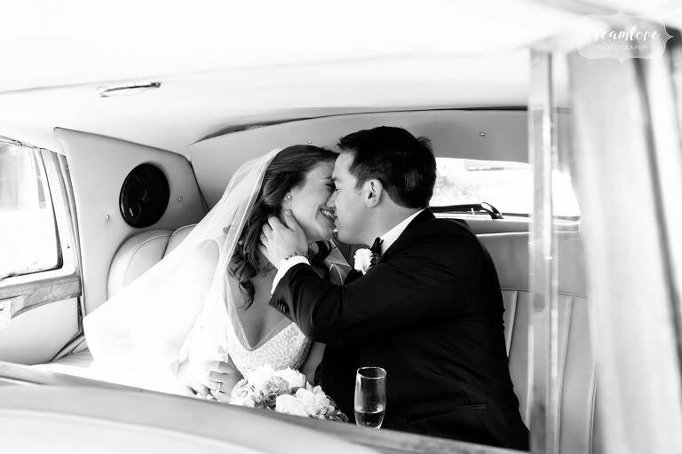 Bride and groom kiss in back of 1948 Rolls Royce in Ipswich, MA.