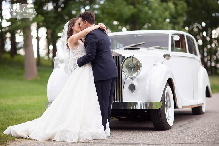 Bride and groom kiss in front of antique car in Ipswich, MA.