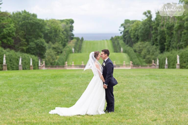 Bride and groom kiss on lawn at Crane Estate for Ipswich MA wedding.