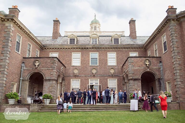 Guests mingle behind the Great House during the cocktail hour at Ipswich MA wedding.