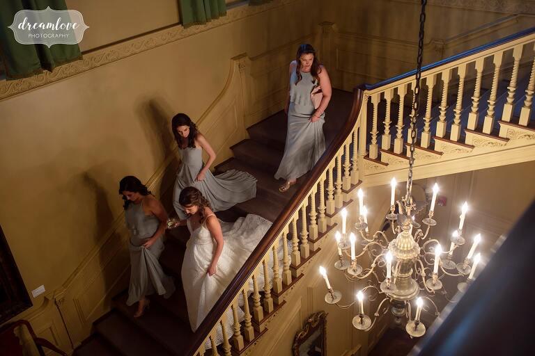 Bride walks down staircase at Crane Estate in Ipswich, MA.
