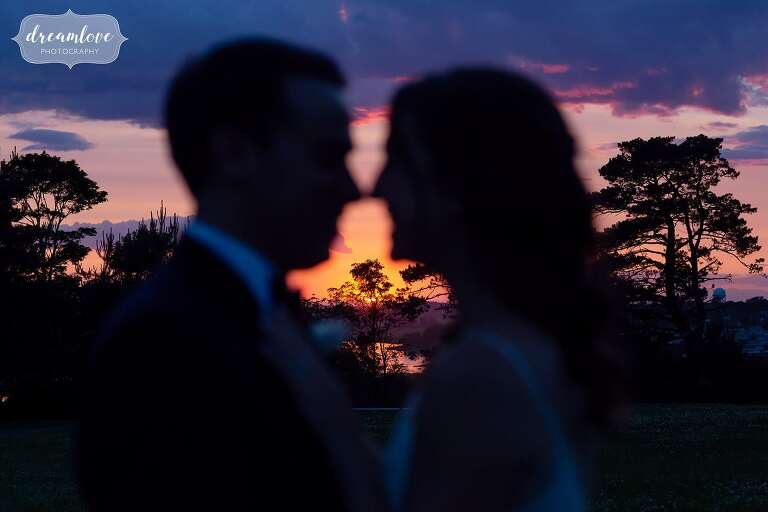 Bride and groom silhouette against sunset at Ipswich MA wedding.