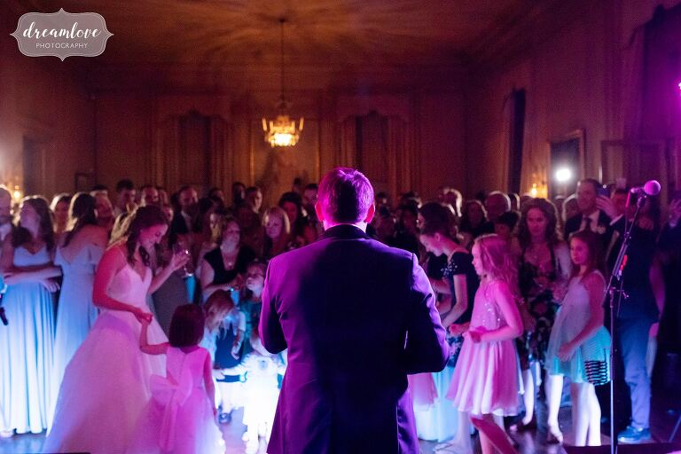 Artistic wedding photo of groom singing the Gambler at Crane Estate.