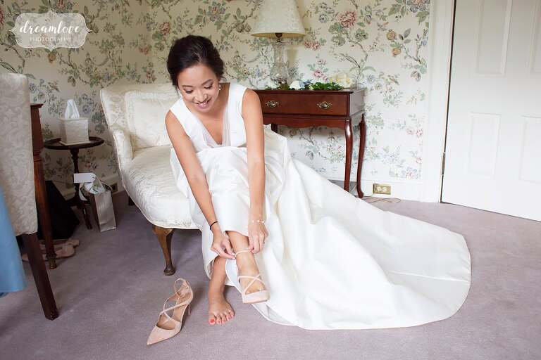 Bride putting on shoes at south shore estate wedding.