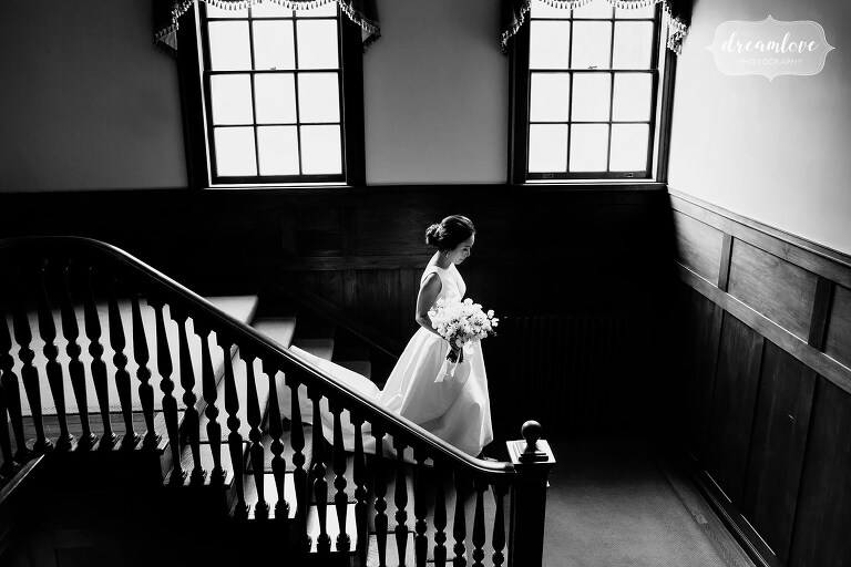 Bride walks down stairs at Bradley Estate with light pouring in through the windows.