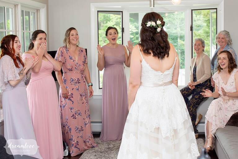Bride surprises bridesmaids with her dress on at Warfield House Inn.