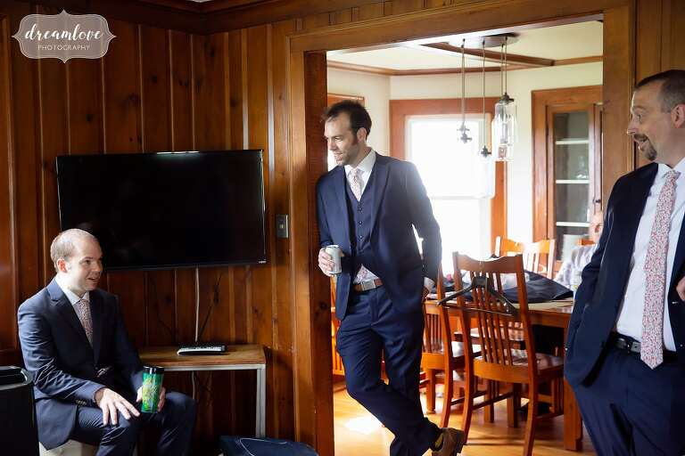 Groom hanging out with groomsmen in bungalow at this Western Mass wedding
