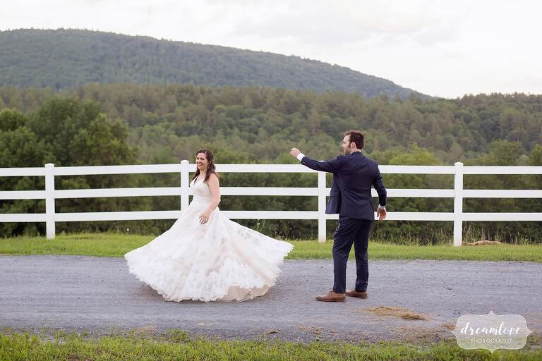 Bride spins in her dress with horse fencing at Warfield House Inn.