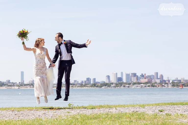 The bride and groom jump at their Thompson Island Boston wedding with the skyline.