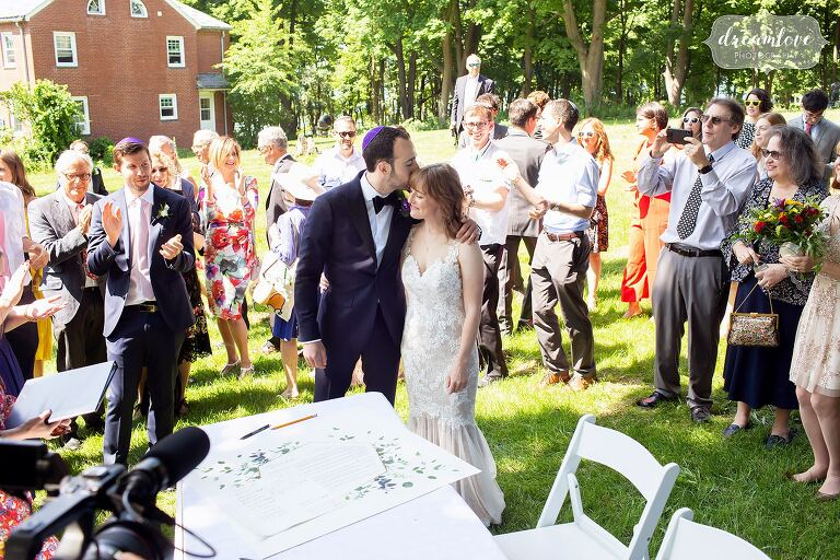 Groom kisses bride after signing their Ketubah on Thompson Island.