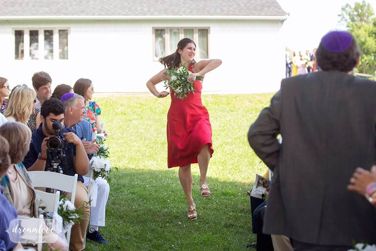 Bridesmaid dancing down the aisle at Thompson Island Boston wedding.