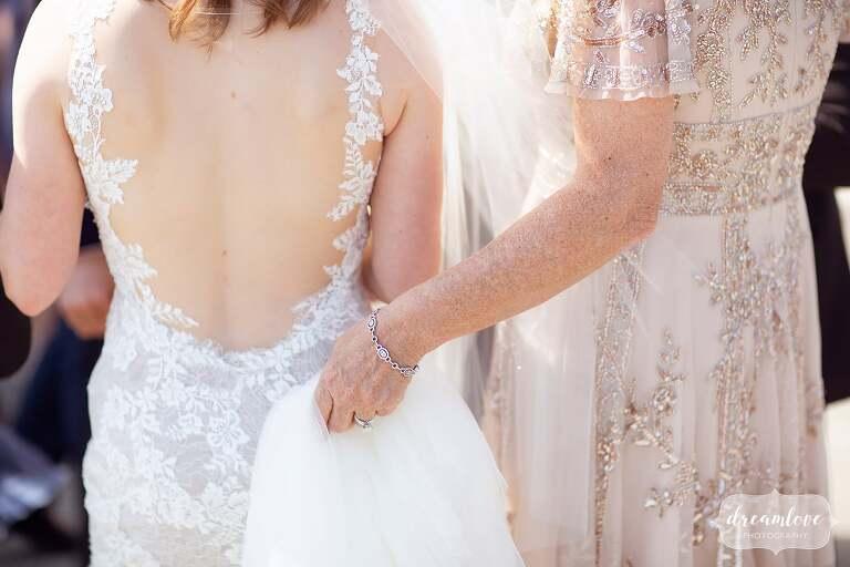 Ethereal wedding photo of mom holding bride's dress.
