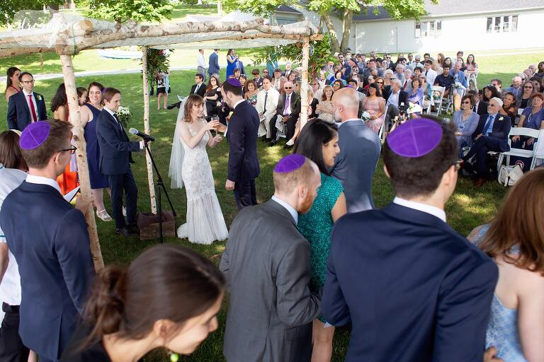 Guests gather around bride and groom during Jewish wedding on Thompson Island.