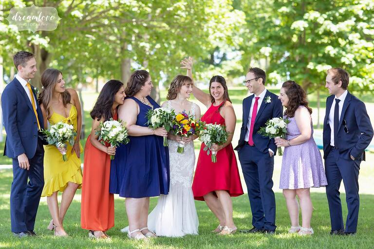 Colorful wedding party under trees at rustic Thompson Island venue.
