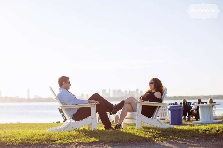 Wedding guests relax in Adirondack chairs overlooking Boston Harbor.