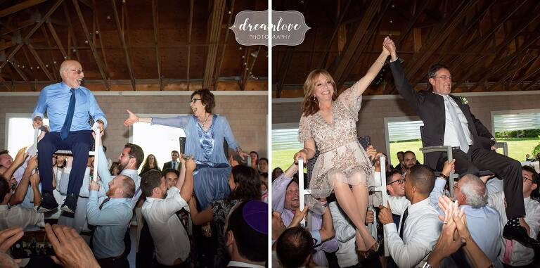 Parents lifted up in chairs during the hora at Boston Jewish wedding.