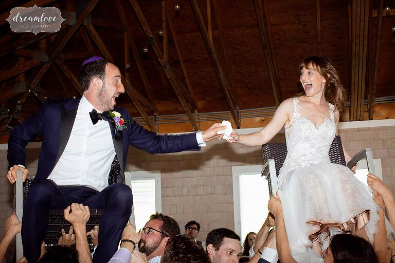 Bride and groom terrified up on chairs during hora at Thompson Island Boston wedding.