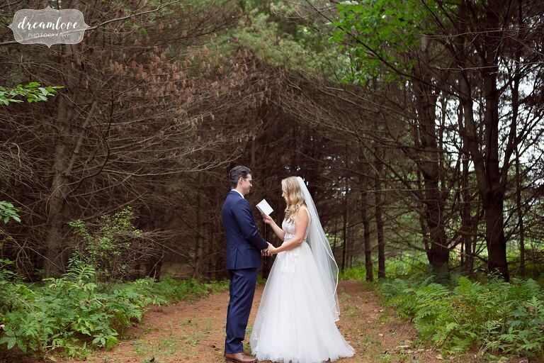 Woodsy wedding bride and groom read vows in pine forest at Bishop Farm.