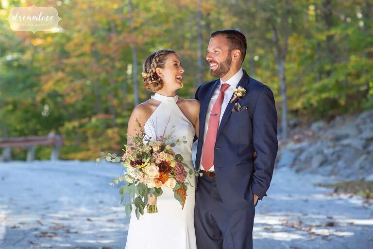 Bride and groom surrounded by fall foliage.