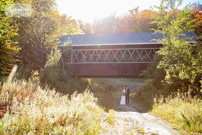 Bride and groom stand under a red covered bridge in Vermont.