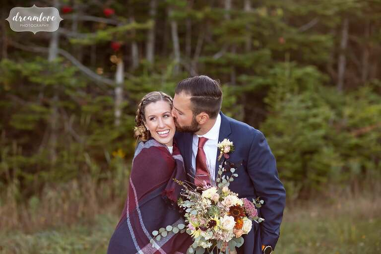 Bride wrapped in a plaid blanket on top of Stratton Mountain.