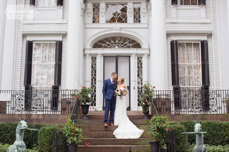 Bride and groom standing on steps of historic mansion, captured by RI wedding photographer.