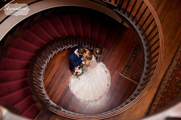 Bride and groom stand at base of spiral staircase in Linden Place, RI.