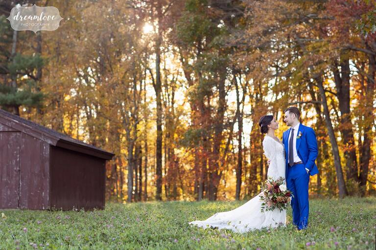 Bride and groom in the field at their Zukas Barn fall wedding in central MA.