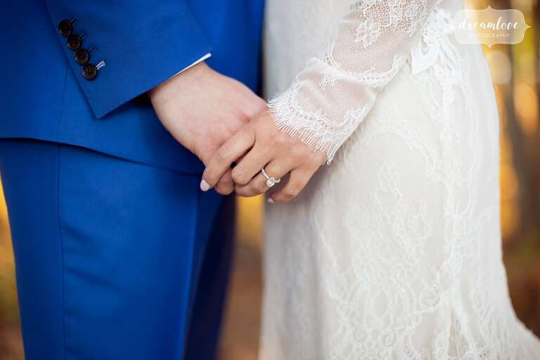 Bride with eyelash lace wedding sleeves holds hand with groom in MA.