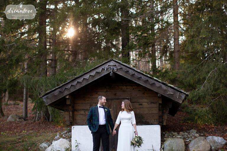 Bride and groom stand in front of rustic cabin at their Vermont ski resort wedding at Stratton.