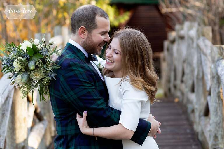 Happy wedding photo of bride and groom laughing on footbridge at Stratton Mountain.