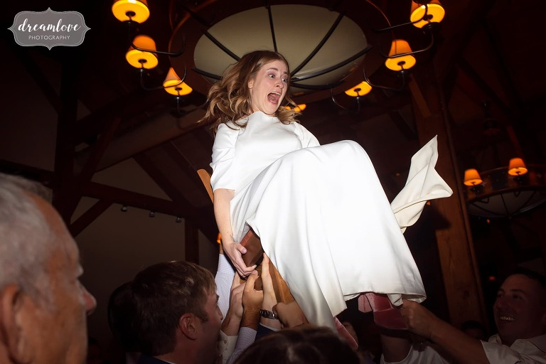 Great documentary photo of terrified bride being lifted up on chair during hora at Stratton Mountain.
