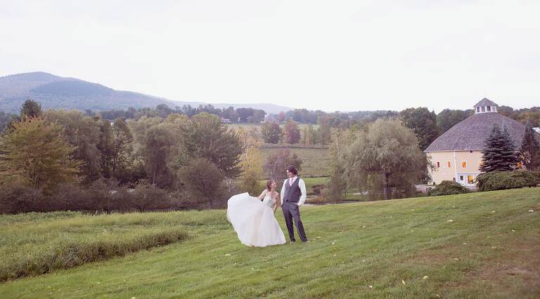 bride and groom in front of round barn farm wedding venue in vermont