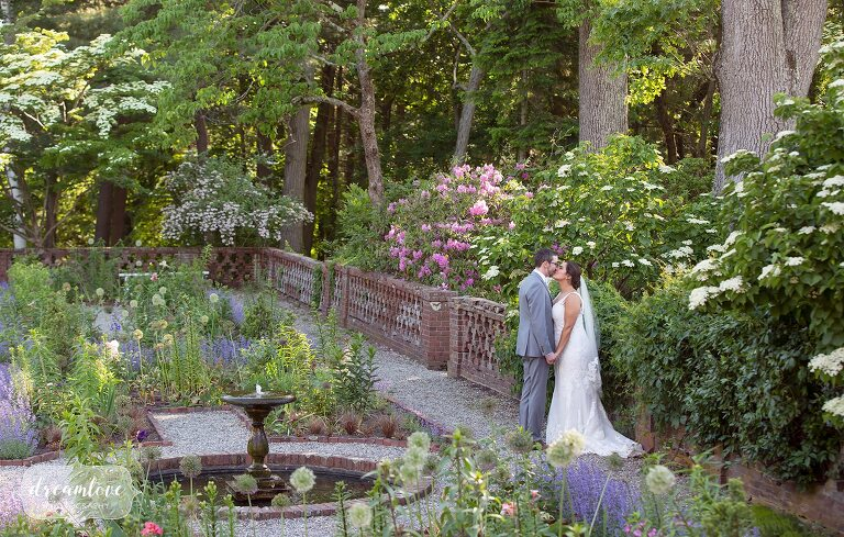 Bride and groom kiss in the english garden behind the Bradley Estate venue in MA.