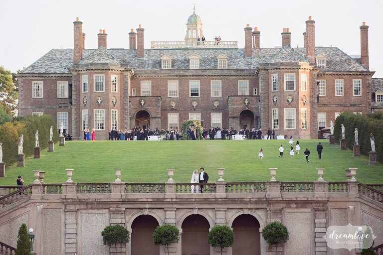 Bride and groom stand in front of the Castle wedding venue at the Crane Estate.